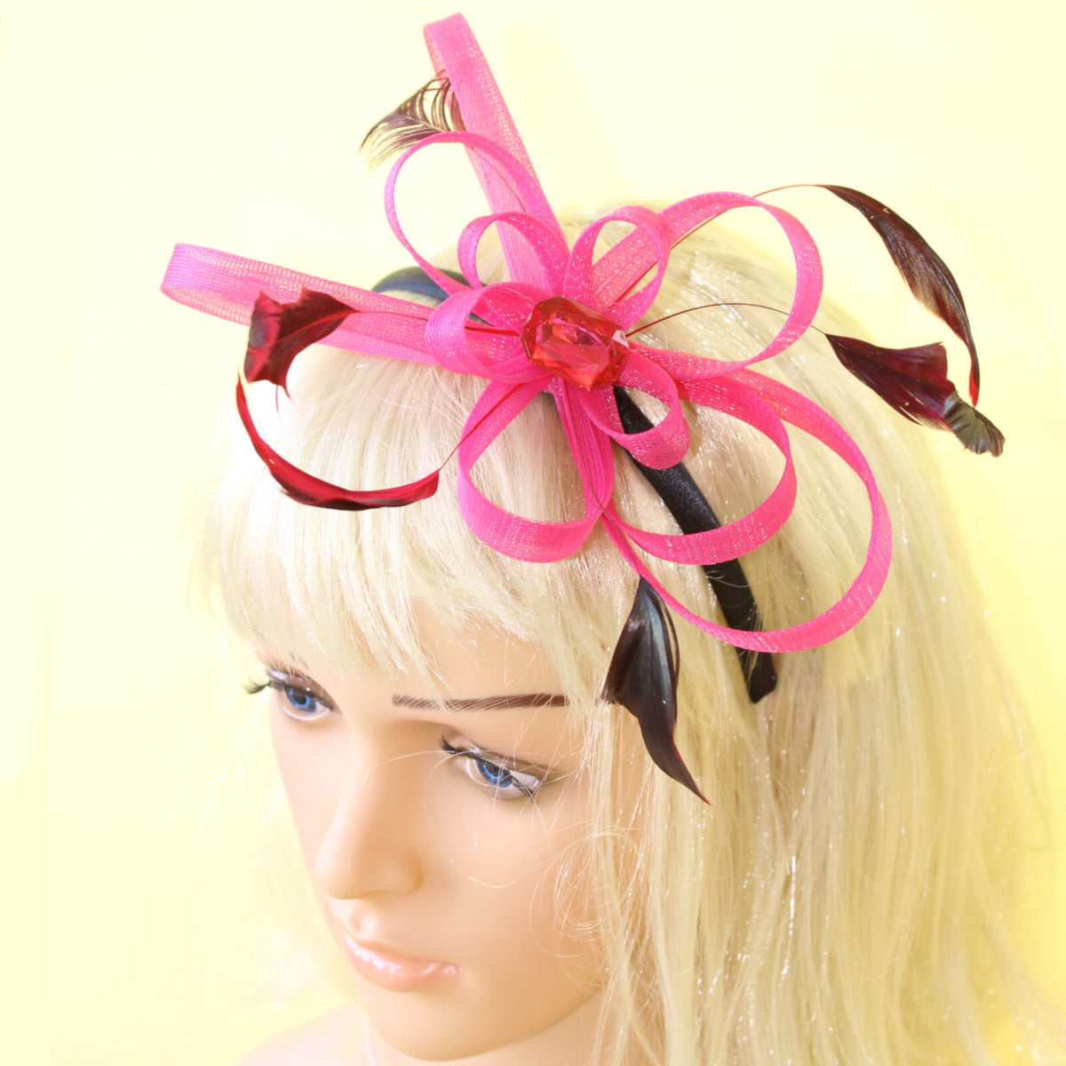 Pink fascinator with loops, gem and feathers on a black aliceband