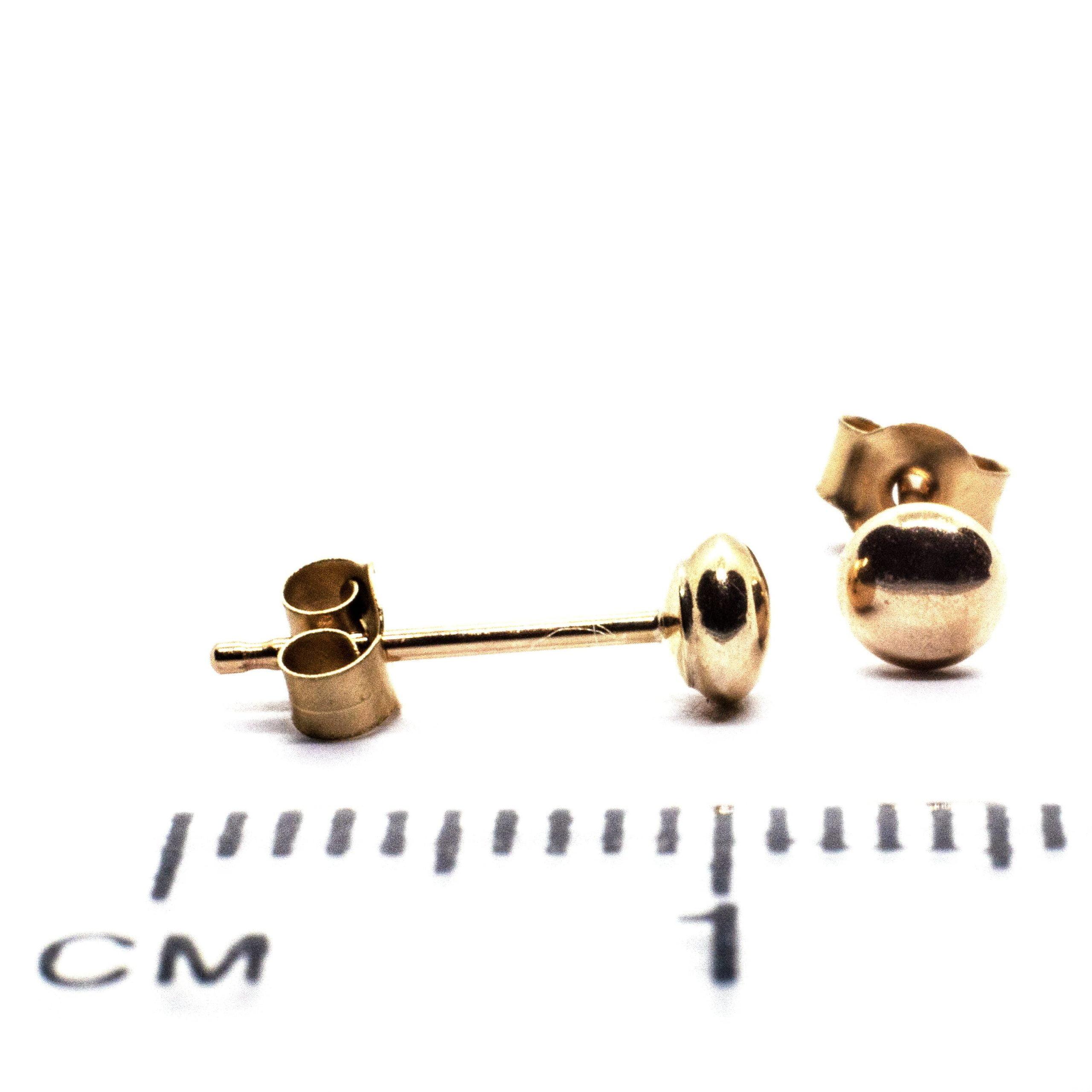 3mm gold bouton earring against ruler