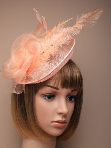 Ladies peach fascinator on alice band. With feathers and net flower.