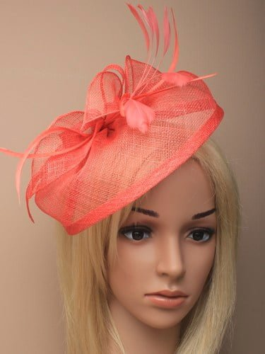 Large coral fascinator with bows, leaves and feathers on an aliceband.