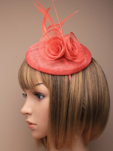 Coral fascinator with simulated flower and feathers on aliceband.