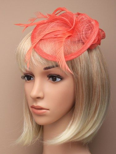 Coral fascinator with simulated roses and feathers on aliceband.