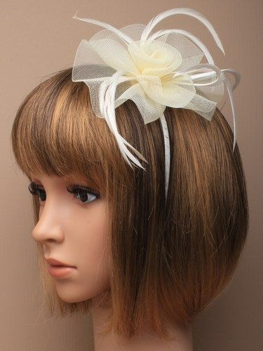 Cream fascinator with simulated flower and feathers on aliceband.
